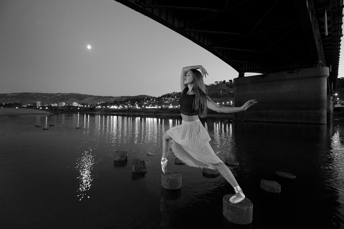 A beautiful, young ballet dancer poses under the Overlander bridge, on the Thompson river, Kamloops, Thompson Okangan region, British Columbia, Canada