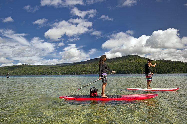 Stand up paddlers enjoy Johnson Lake, south of Barriere, Thompson Okangan region, British Columbia, Canada