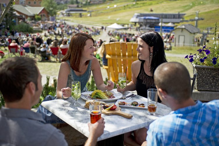 Tourists enjoy a meal at an outside patio, Sun Peaks resort, north of Kamloops, British Columbia, Canada