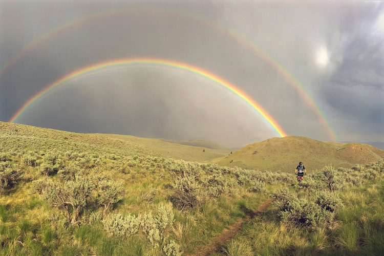 A mountain biker takes on an epic ride during a double rainbow in the protected Lac Du Bois grasslands near Kamloops, British Columbia, Thompson Okanagan region, Canada
