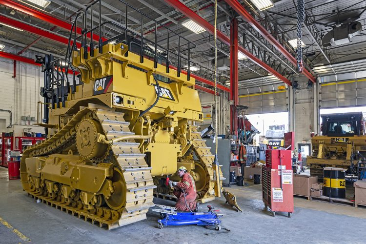 Image of a mechanic working on a large cat machine during a commercial heavy duty industry shoot for the Kamloops facilities of Finning, Canada