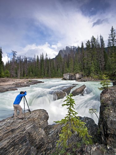 A photographer capture the 'Natural Bridge' in Yoho National Park, Rocky Mountain region, British Columbia, Canada