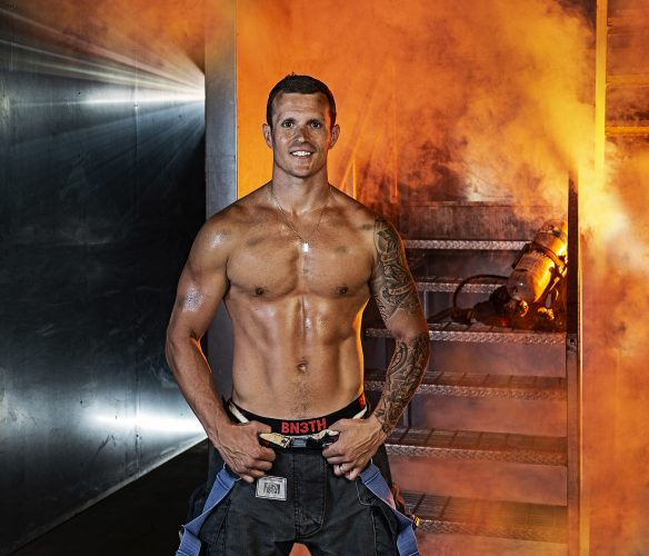 A firefighter poses for a portrait for the annual Kamloops firefighter's calendar in their training center, Kamloops, British Columbia, Canada