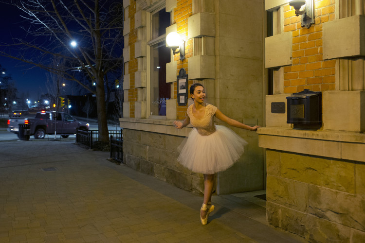 A female balleina poses on Victoria street in Kamloops, Thompson Okanagan region, British Columbia Canada,