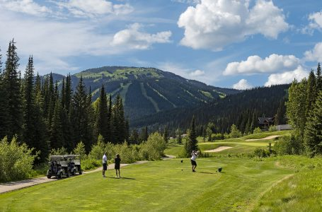 A group of golfers tee off at a par 3 on Sun Peaks' famed golf course during a commercial shoot, British Columbia, Thompson Okanagan region, Canada