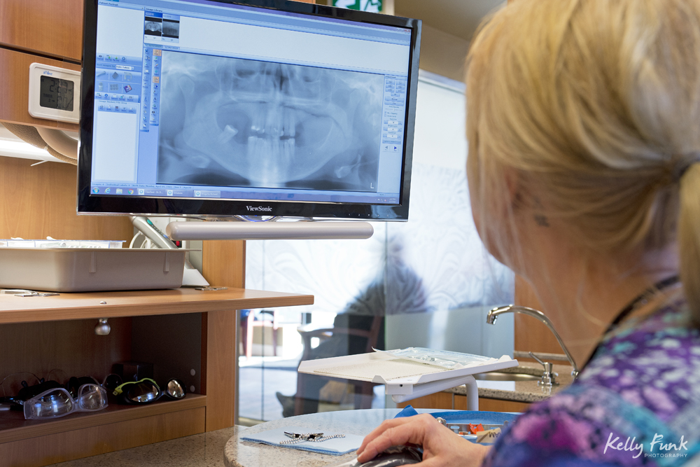 A certified dental assistant looks at x-rays at Sagehills Dental Clinic, located in Kamloops, British Columbia, Thompson Okanagan region, Canada, during a commercial photo shoot