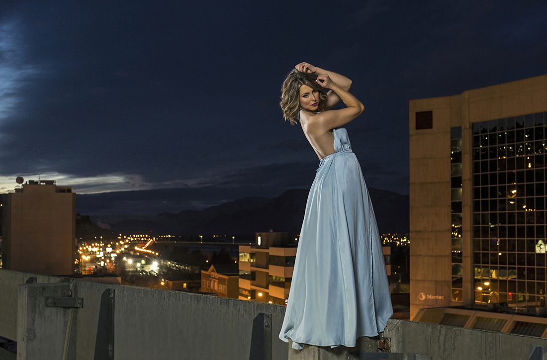 Portrait of a beautiful woman in a pose over the city of Kamloops at night with lights, BC, Thompson Okanagan region, Canada