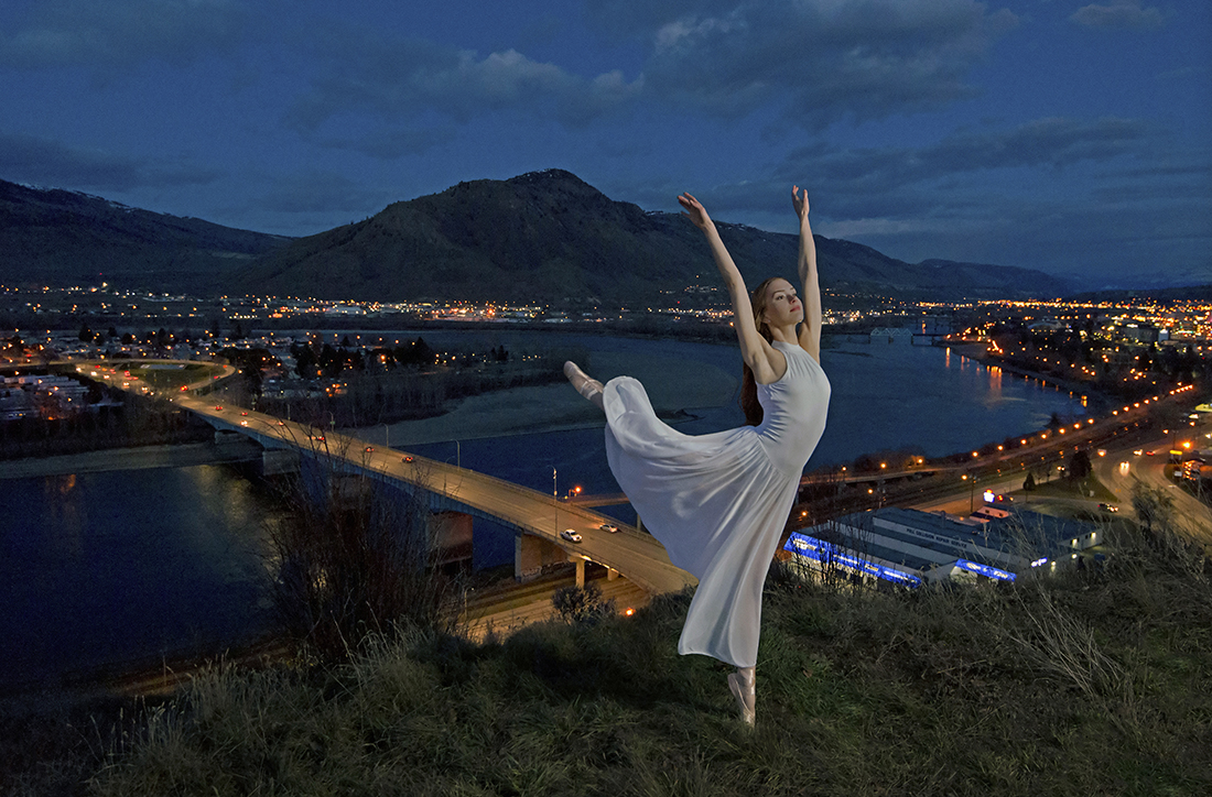 Ballerina strikes a pose over the city of Kamloops, BC, Canada at night with lights.