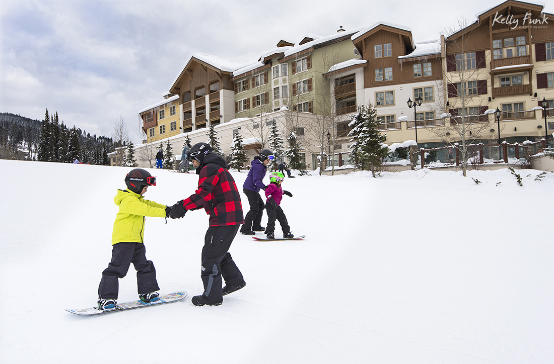 Parents teach kids snow boarding at Sun Peaks resort, near Kamloops, British Columbia, Canada