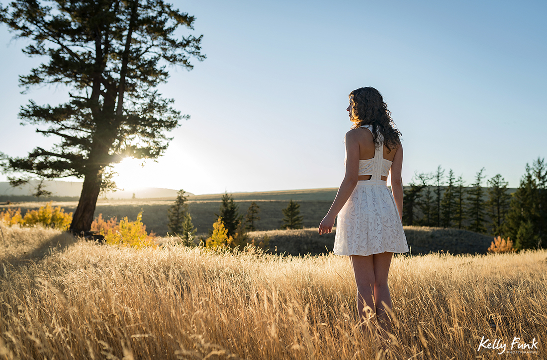 A young woman enjoys a gorgeous sunset in the grasslands of British Columbia, Canada during a commercial photo shoot