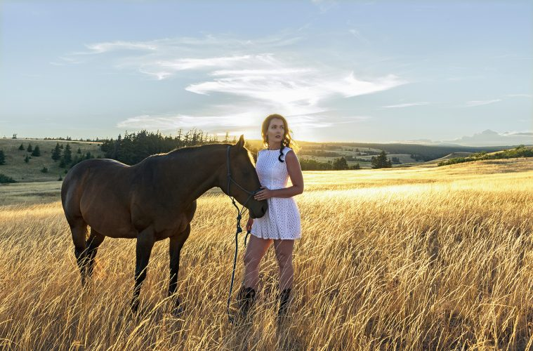 A beautiful young woman and her horse pose at sunset for a stylized portrait, Kamloops, British Columbia, Canada