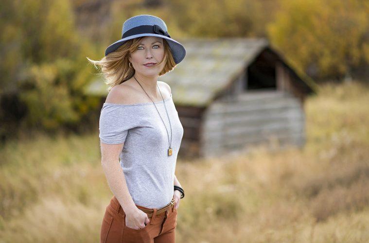Stylized shoot of a young, beautiful woman in a field, Kamloops, Thompson Okanagan region, British Columbia, Canada