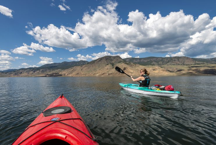 Kayakers travel west on Kamloops Lake, Thompson Okanagan region of British Columbia, Canada