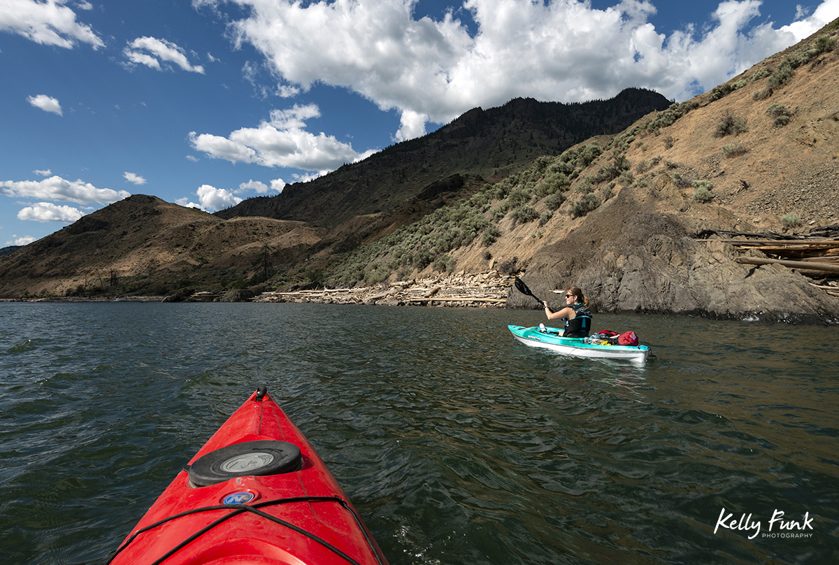 Kayakers travel west on Kamloops Lake for an assignment, Thompson Okanagan region of British Columbia, Canada