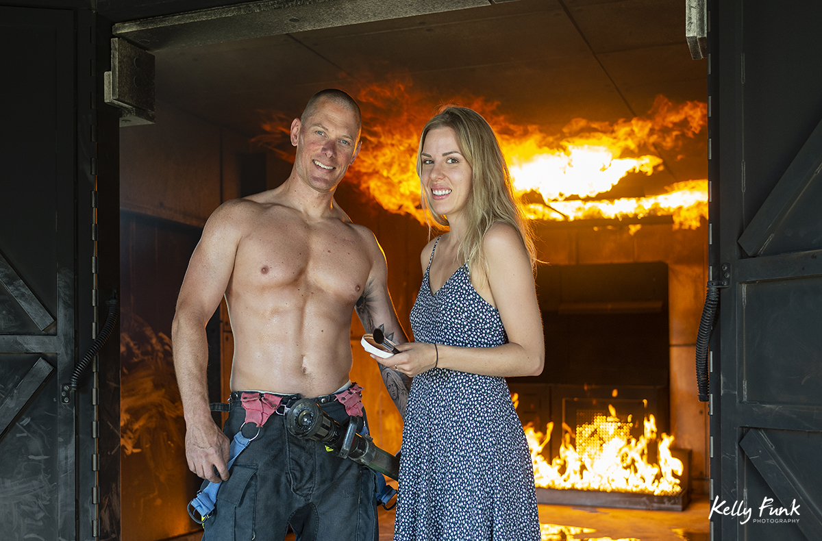Hair and makeup specialist and a fire fighter pose during shooting for the 2019 Kamloops fire fighters calendar, Thompson Okanagan region, British Columbia, Canada