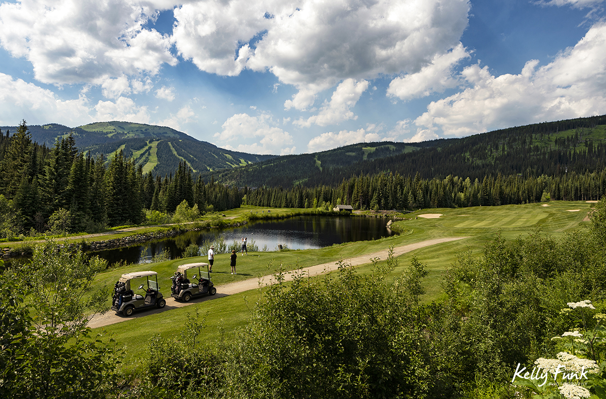 A man tees off on a back nine hole, while friends look on at the Sun Peaks Resort golf course, north east of Kamloops, British Columbia, Thompson Okanagan region, Canada