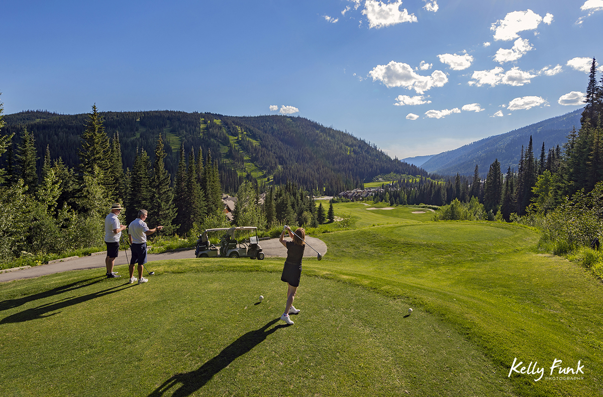 A woman tees off at the elevated 16th hole at the Sun Peaks Resort golf course, north east of Kamloops, British Columbia, Thompson Okanagan region, Canada