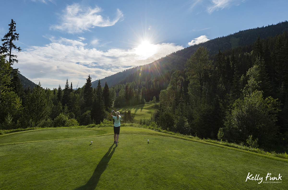 A young woman tees off at sunset at the Sun Peaks Resort golf course, north east of Kamloops, British Columbia, Thompson Okanagan region, Canada