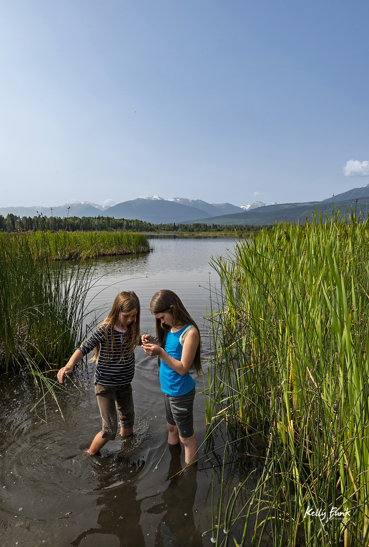Two girls enjoy the cranberry marsh in the morning, Valemount, British Columbia, Canada