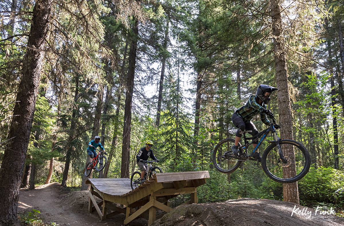 a group of riders ride the wave at the bike park in Valemount, British Columbia, Canada