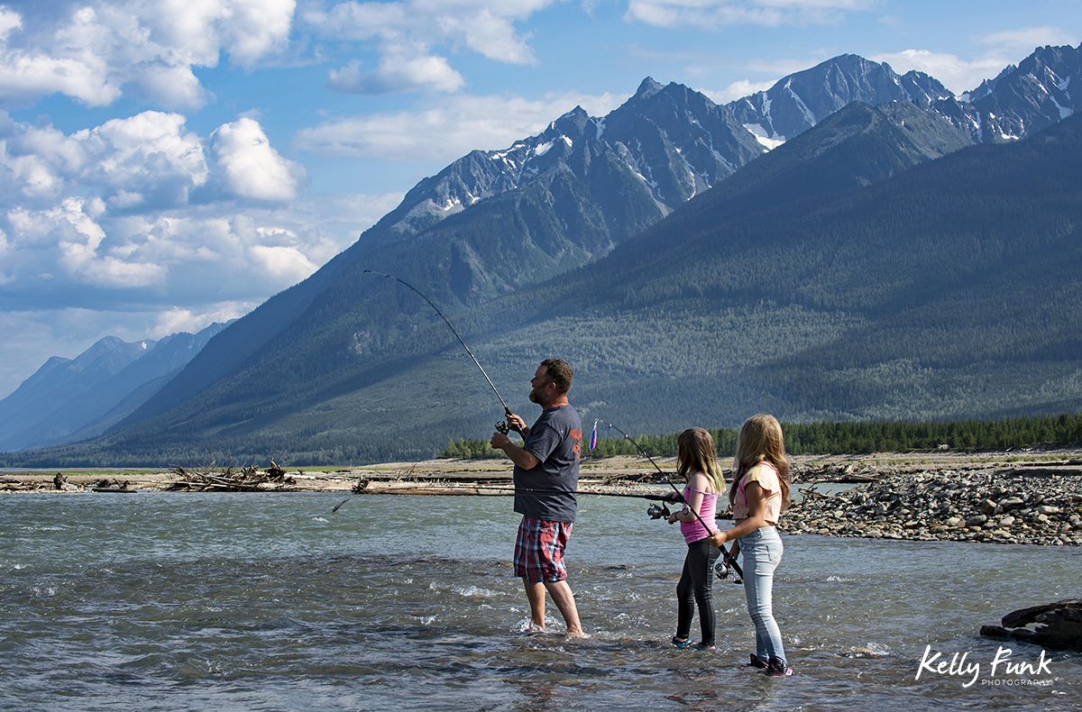 A father and his two girls fish in a river near Kinbasket Lake, British Columbia, Canada