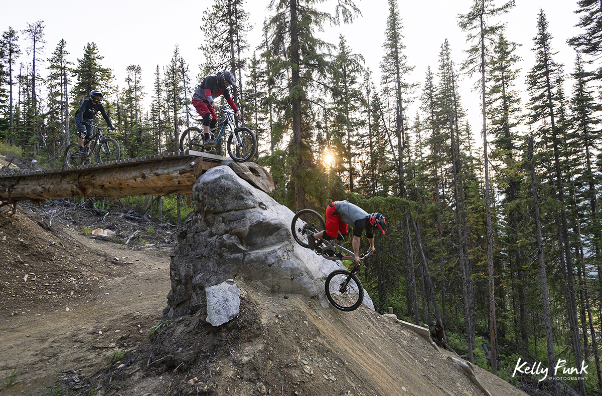 A group of riders take on a rugged feature at the top of the bike park in Valemount, British Columbia, Canada