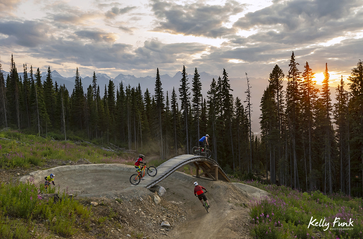 A group of riders take on a rugged jump feature at sunset near the top of the bike park in Valemount, British Columbia, Canada