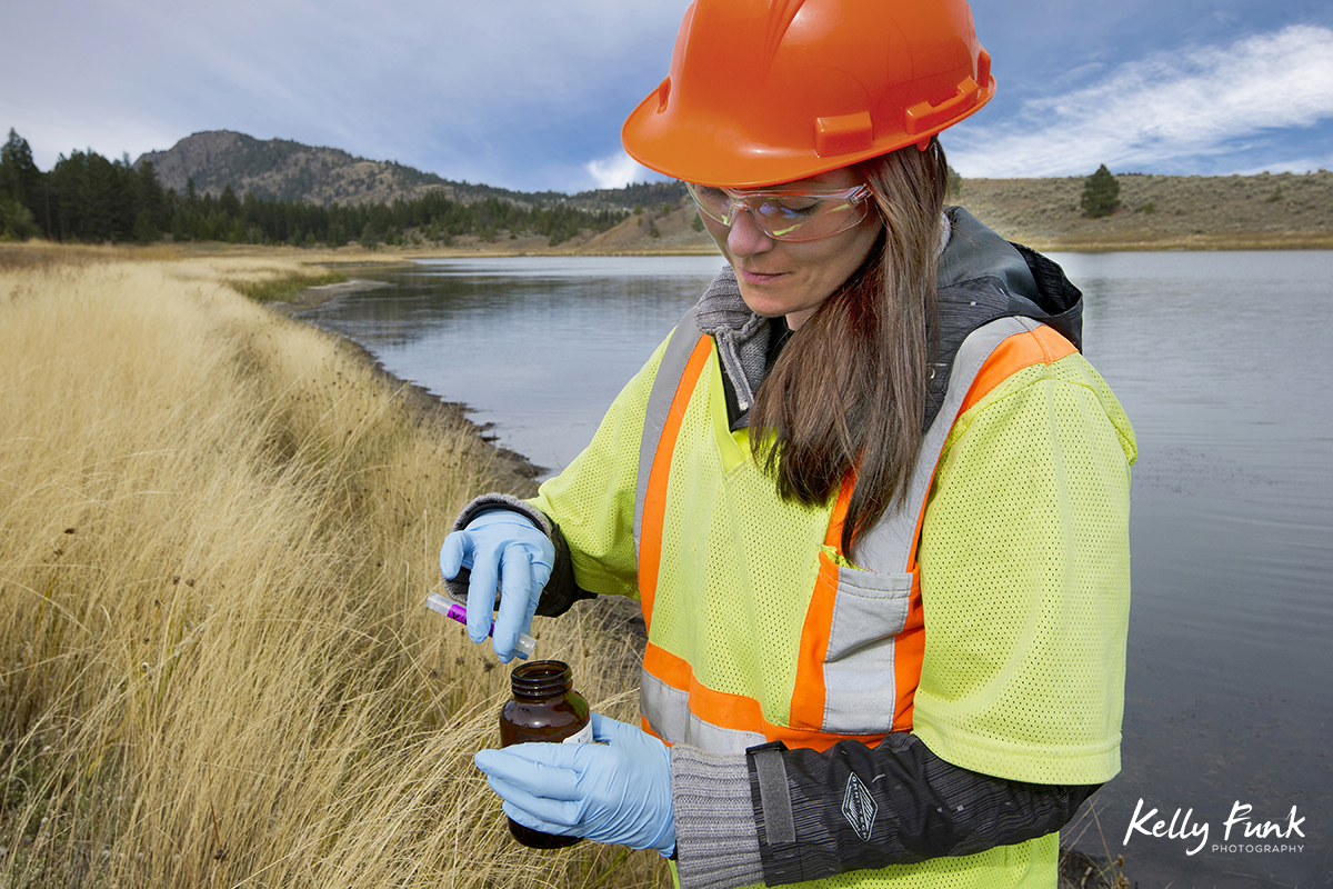 A scientist takes a water sample at an industrial site, British Columbia, Canada