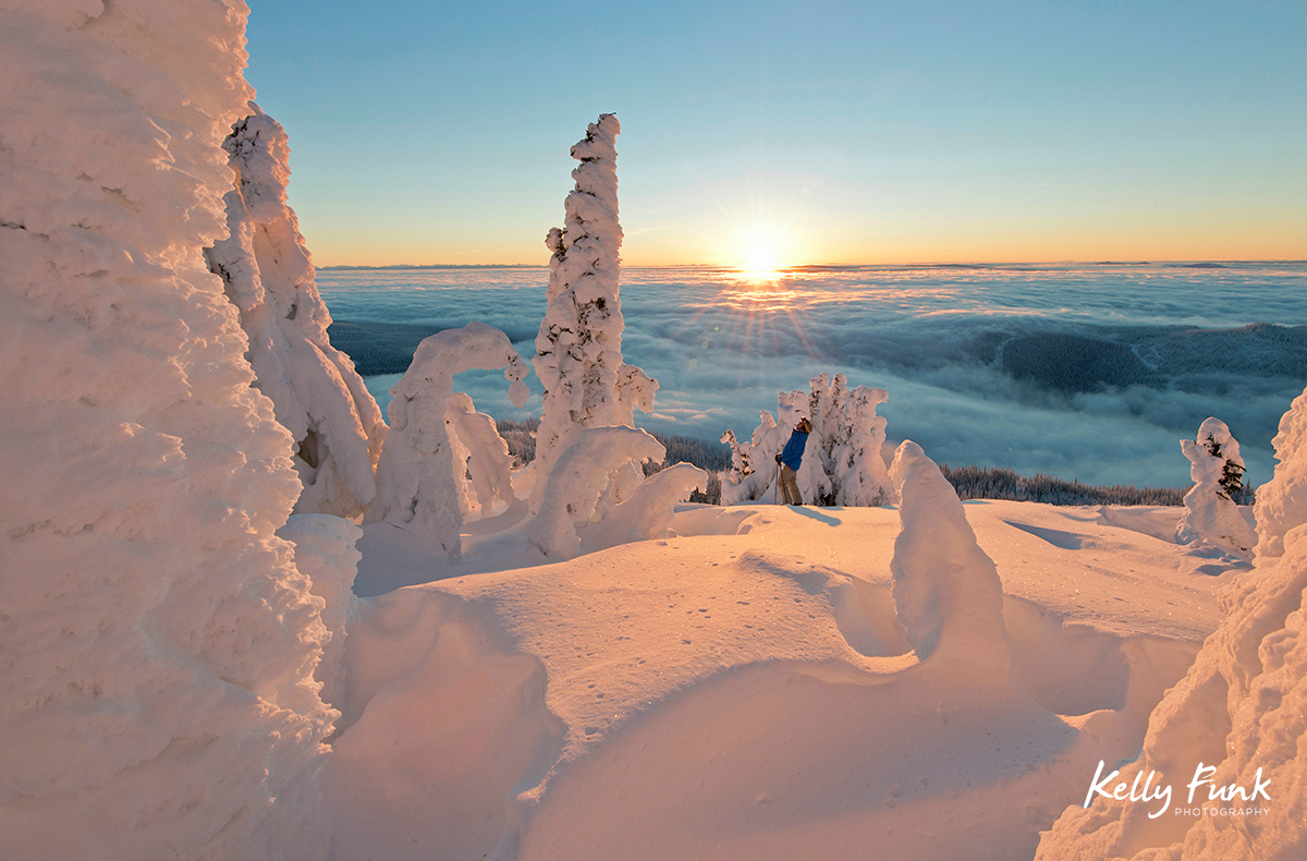 A skier rests among the snow ghosts while surveying the beautiful landscape at sunrise at the top of Sun Peaks Resort, Thompson Okangan region, British Columbia, Canada