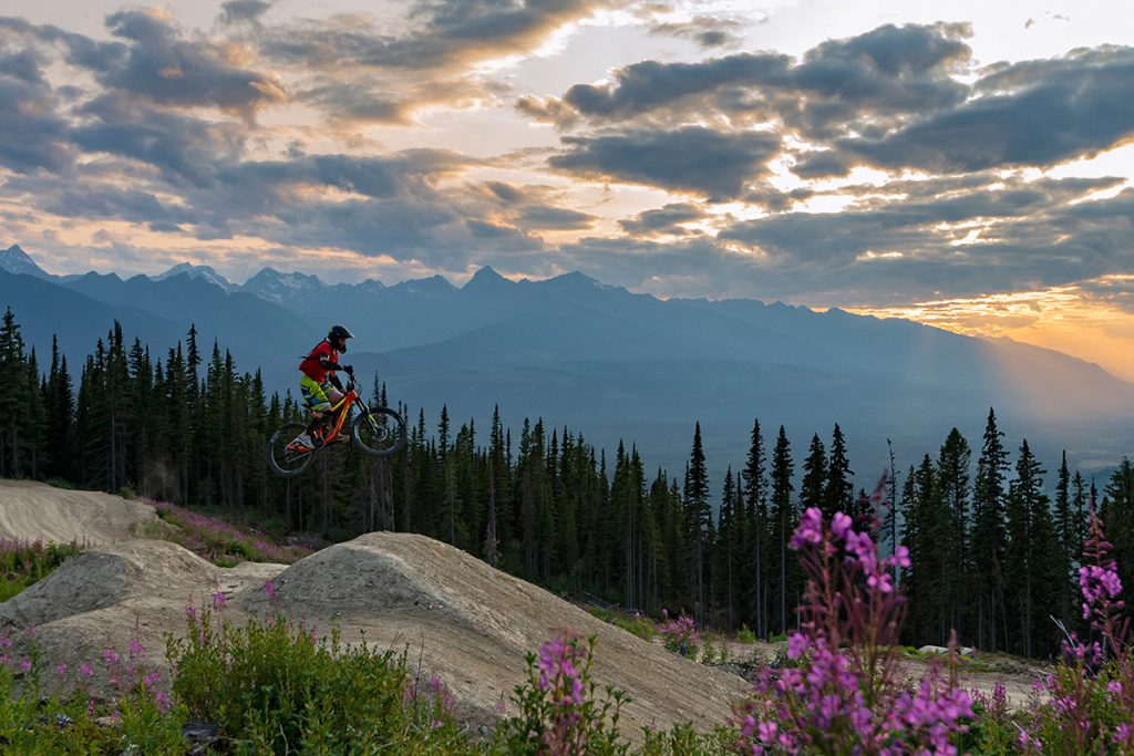 A single rider take on a rugged jump feature at sunset near the top of the bike park in Valemount, British Columbia, Canada