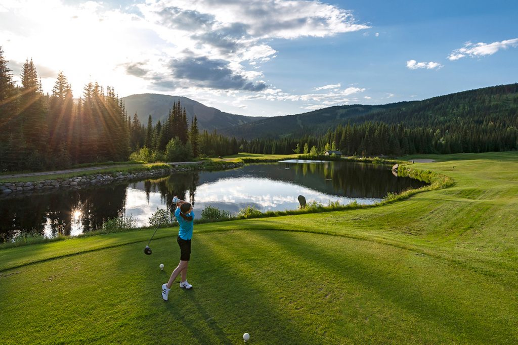 A young golfer tees off on a beautiful evening at Sun Peaks Resort golf course, British Columbia, Canada