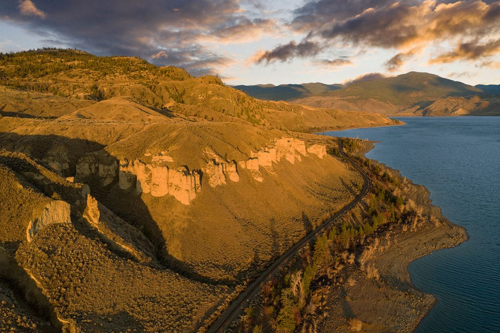 Aerial / drone of the CN rail line cuts the morning landscape near Tobiano resort west of Kamloops, British Columbia, Canada