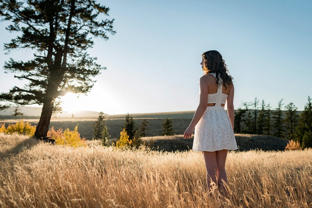 A stylish, young, beautiful woman in the fall grasslands, Kamloops, Thompson Okanagan region, British Columbia, Canada