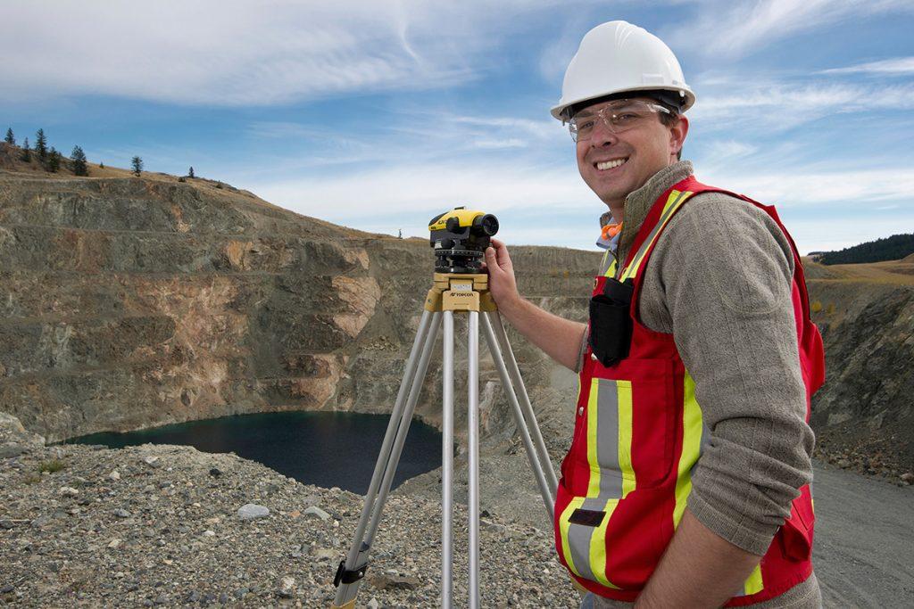A surveyor studies the landscape of a mine near Kamloops, British Columbia, Canada